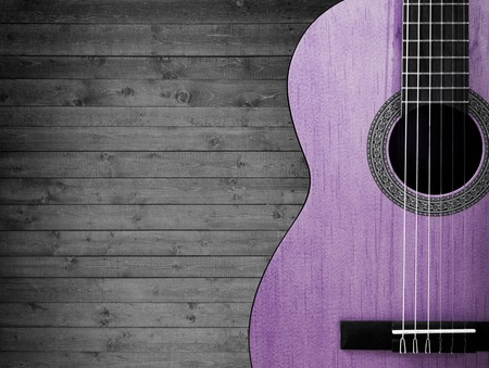 bluegrass: Part of a pink acoustic guitar on a gray wooden background Stock Photo