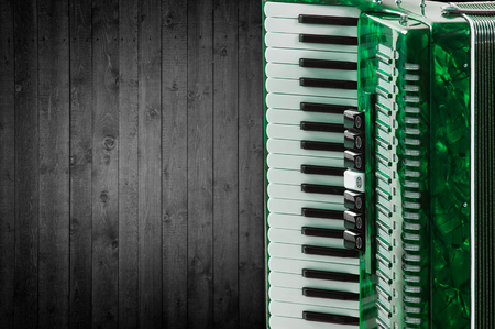 overtone: Part green accordion on wooden grey background. Write text.
