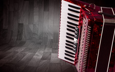 overtone: Part red accordion on wooden grey background. Write text.