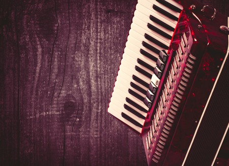 overtone: Part red accordion on wooden grey background. Write text. Vintage. Stock Photo