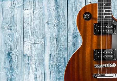 Part of the orange electric guitar on wooden background. A place for writing of the text 스톡 콘텐츠