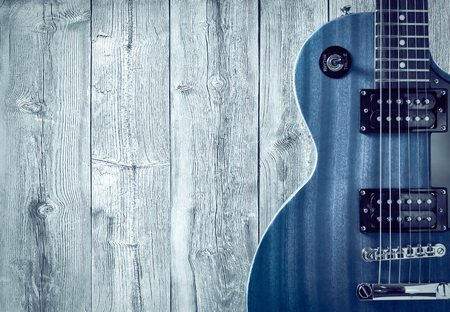 Part of the blue electric guitar on wooden background. A place for writing of the text 스톡 콘텐츠