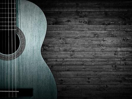 Parte de una guitarra acústica azul sobre un fondo de madera gris