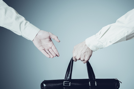 handover: business transfer deal. handover of a suitcase for money partners. Stock Photo