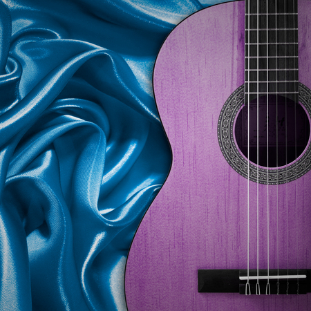 Part of a blue acoustic guitar on silk background