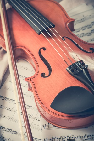 sheet music: Old violin lying on the sheet of music, music concept. Stock Photo