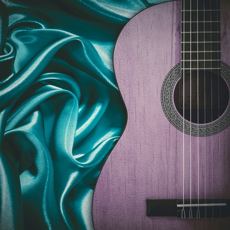 fingerboard: Part of a blue acoustic guitar on silk background