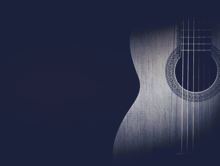 fingerboard: Part of a blue acoustic guitar on black background