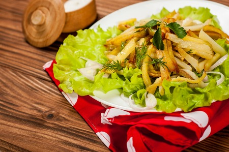 fried potatoes: Fried potatoes on a white plate with herbs on wooden background. Stock Photo