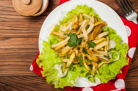fried potatoes: Fried potatoes on a white plate with herbs on wooden background. The view from the top.