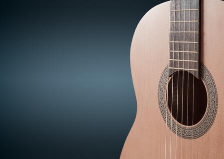 fingerboard: Part of a blue acoustic guitar on black background.