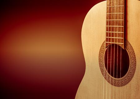 Part of a orange acoustic guitar on black background