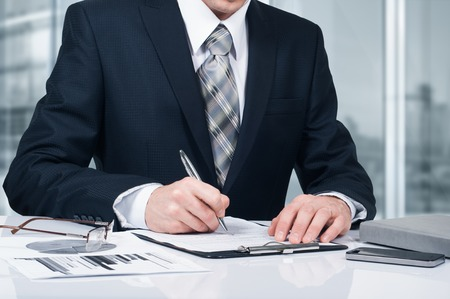 Young businessman signing a contract in office. The concept of a successful business