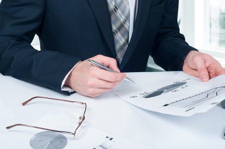 denoting: Businessman analyzing financial figures denoting the progress in the work of the company.