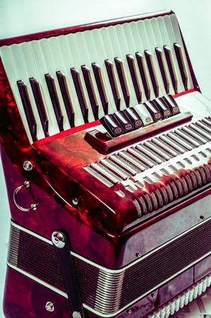 overtone: part red musical instrument accordion, white background. Stock Photo