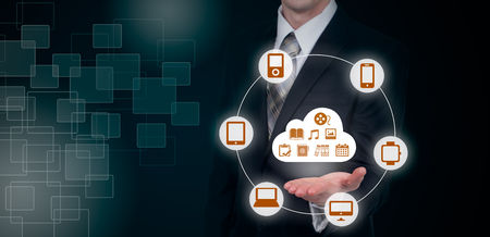 Businessman touching a cloud connected to many objects on a virtual screen, concept about internet of things Stock Photo