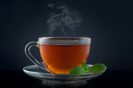 Cup tea with mint on a black background.