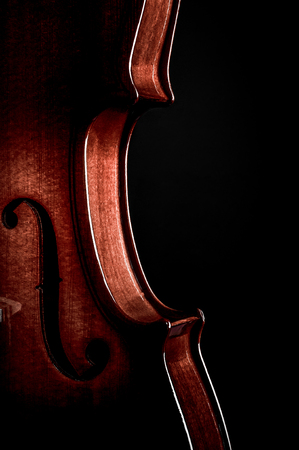 cellos: Violin musical instruments of orchestra closeup on black. Stock Photo
