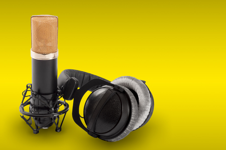 cardioid: Headphones and condenser microphone on the yellow background.