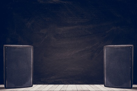 Large black speakers on wooden background with space for text writing