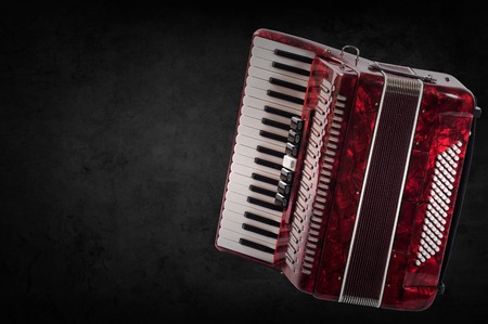 overtone: Red accordion on wooden grey background. Write text.
