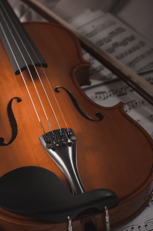 Old violin lying on the sheet of music, music concept. Stock Photo