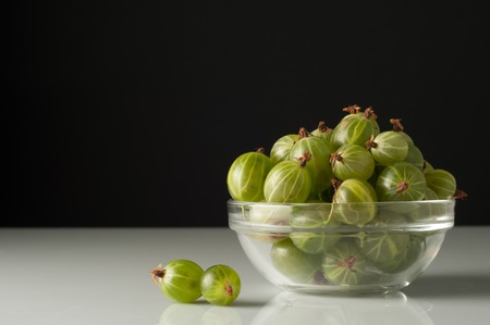 Juicy ripe berries of a gooseberry in a small glass plate on black surface. Gooseberry harvest