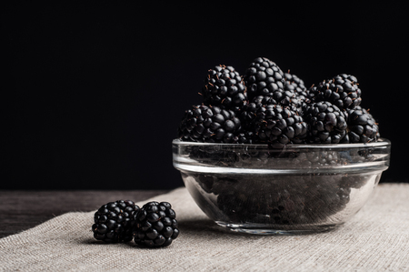 Fresh Ripe Juicy Blackberries in a plate on black background. Stock Photo