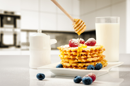 Homemade waffles with berries in plate on white table.