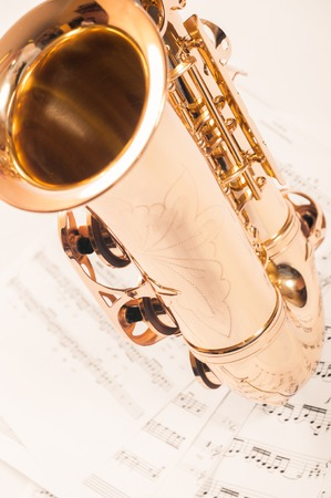 Part of the saxophone lying on the notes. Stock Photo