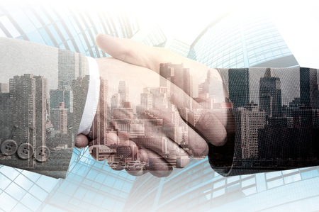 Double exposure of two business people handshake and city.