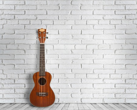 Ukulele guitar on a white wall background. Concept of travel and lifestyle.