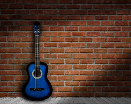 acoustic guitar brick background wall shadow