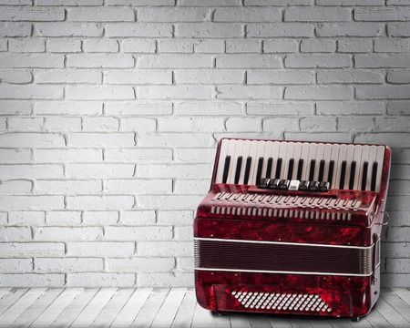 Vintage red accordion on brick wall background
