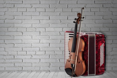 Vintage red accordion and violin on brick wall background. 스톡 콘텐츠