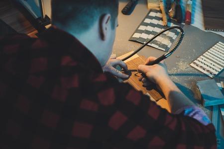 An artist using wood. Handmade use of a drill.
