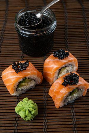 Sushi roll Philadelphia with salmon, smoked eel, avocado, cream cheese on black background. Japanese food.