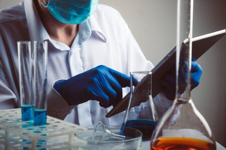 Professional scientist holding a test tube and tablet while making a research.