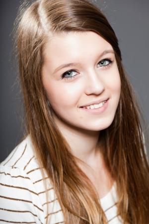 Pretty happy brunette teenage girl. Studio shot. photo