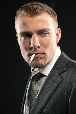 Fashion man in suit smoking cigarette. Studio shot against black. photo