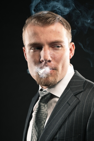 Fashion man in suit smoking cigarette. Studio shot against black. photo