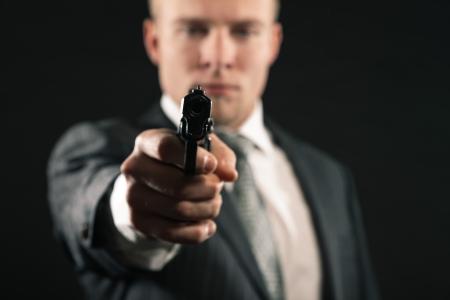 Man in suit shooting with gun. Studio shot against black. Stock Photo - 17803520