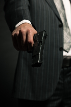 Man in suit shooting with gun  Studio shot against black