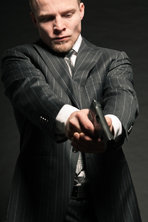 Man in suit shooting with gun  Studio shot against black Stock Photo - 17802516