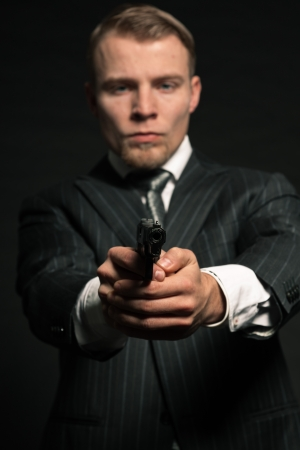 Man in suit shooting with gun  Studio shot against black  photo