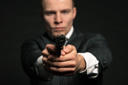 Man in suit shooting with gun  Studio shot against black  photo