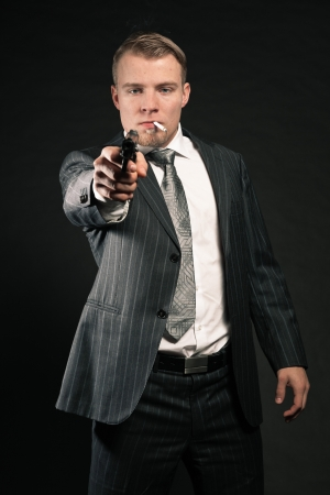 Man in suit shooting with gun  Smoking cigarette  Studio shot  photo