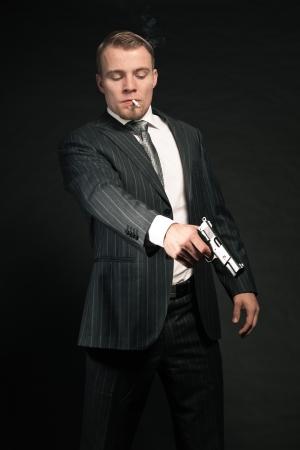 Man in suit shooting with gun  Smoking cigarette  Studio shot  photo
