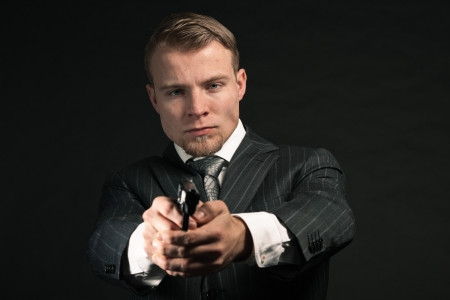 Man in suit shooting with gun. Studio shot against black. photo