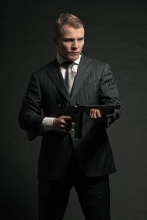 Man in suit shooting with rifle. Studio shot against black. Stock Photo - 17802692